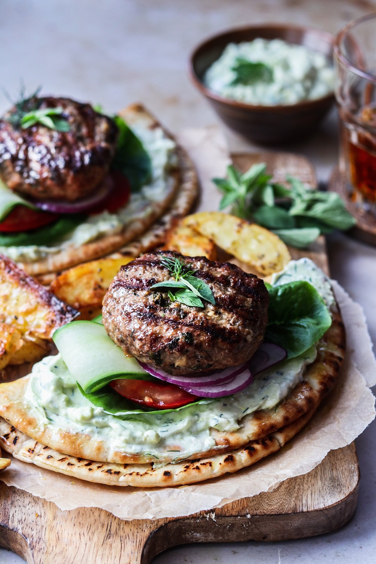Greek lamb burgers served on wooden board with a glass of lager.