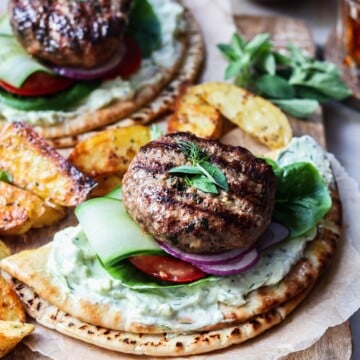 Grilled lamb patties garnished with fresh herbs over tzatziki and veggies on pita bread.