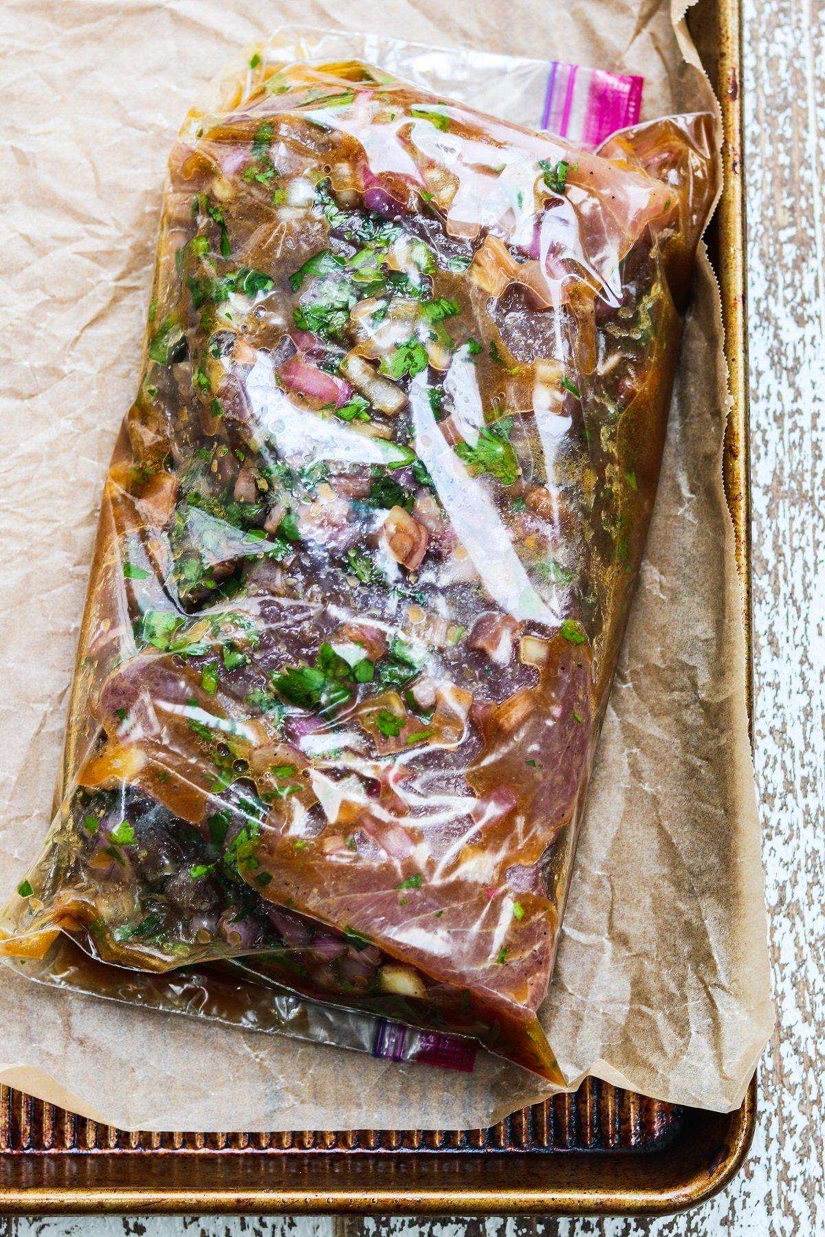 Tuna steaks marinating in resealable plastic bag.