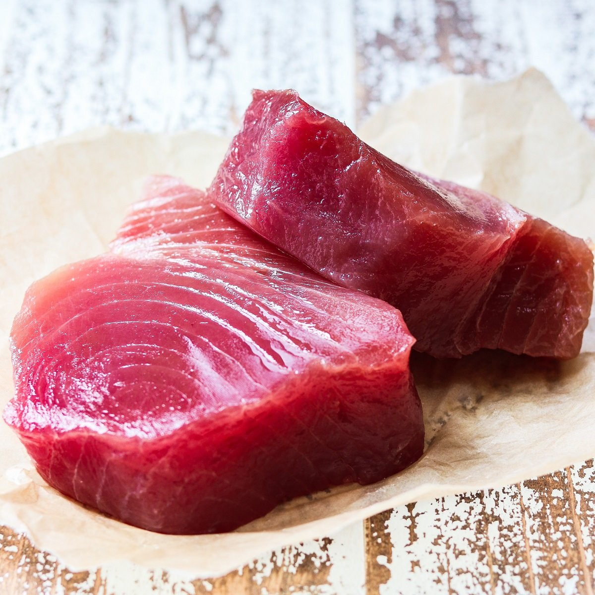 Two 1 ½-inch thick ahi tuna steaks on parchment paper.
