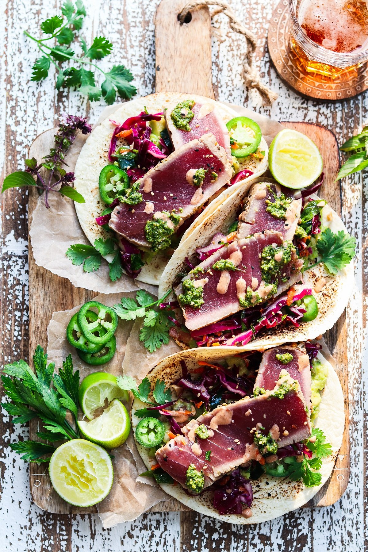 Tuna tacos served with lime wedges, sliced jalapenos and garnished with fresh herbs.