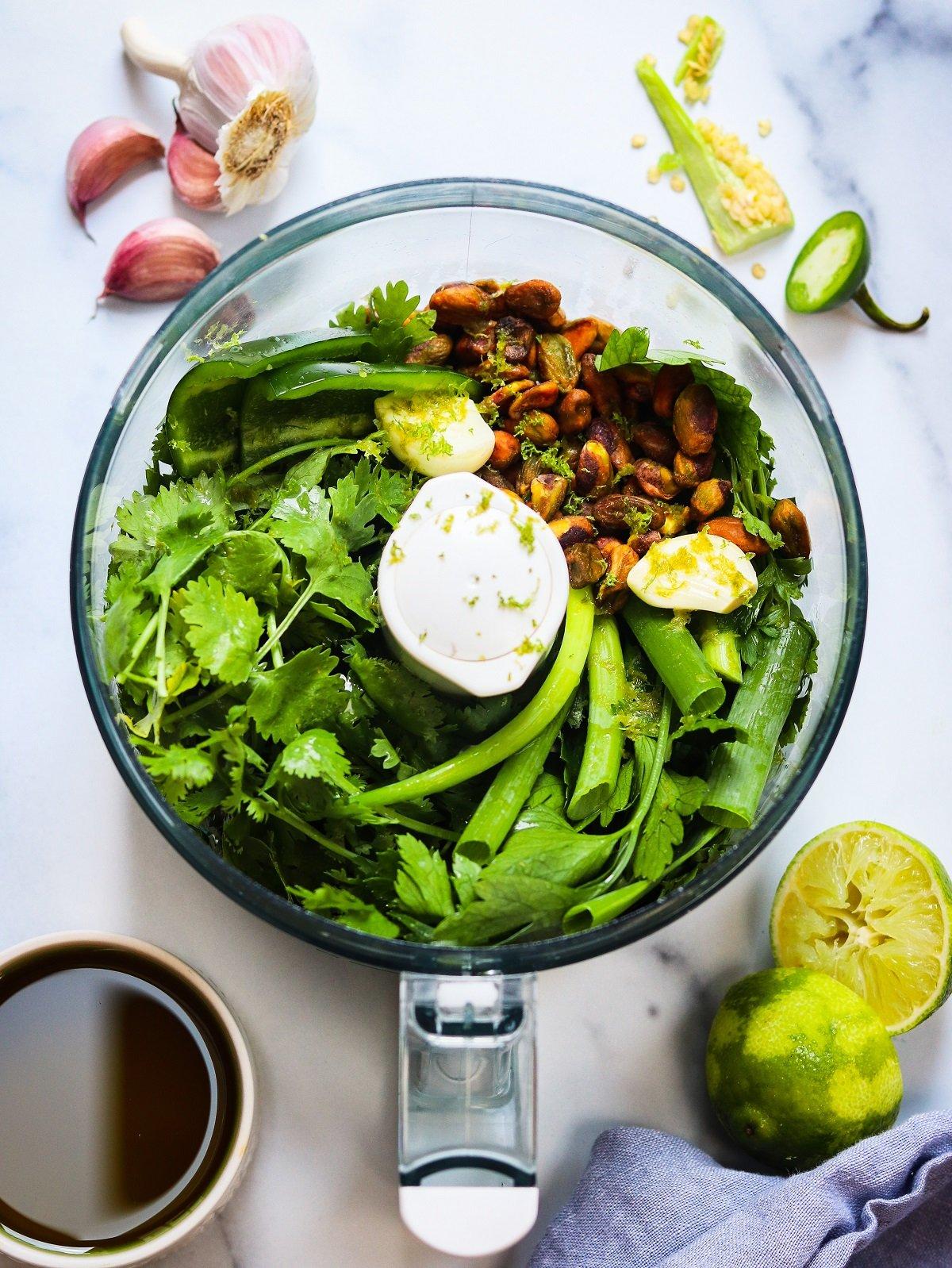 Pesto ingredients in food processor bowl.