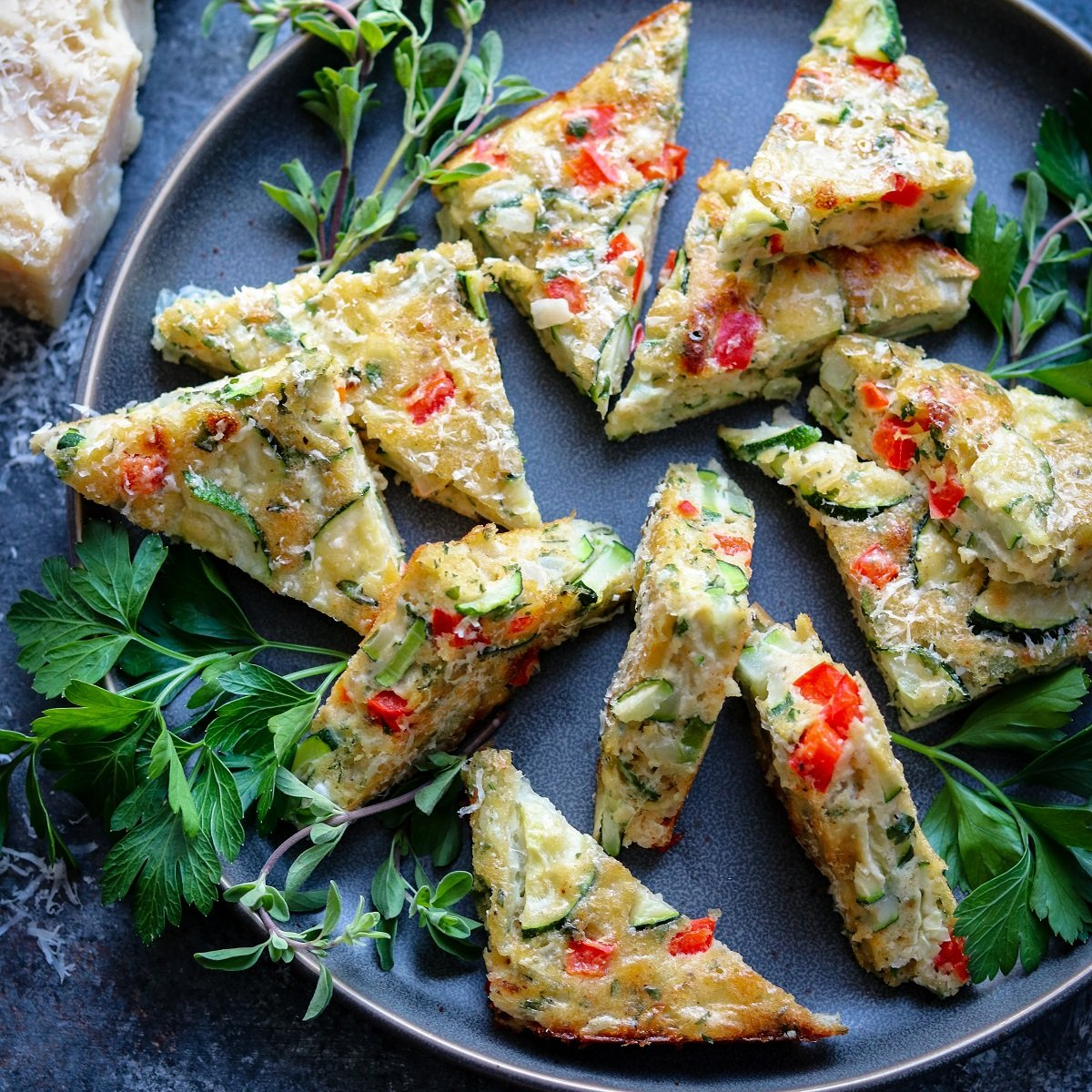Zucchini bites cut into triangles garnished with fresh herbs and served on a gray plate.
