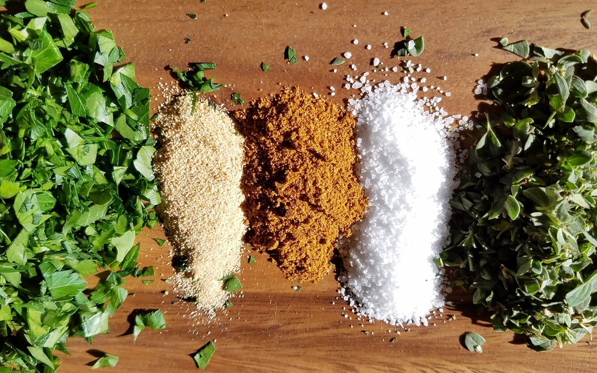 Spices and fresh herbs lined up in piles on wooden board.
