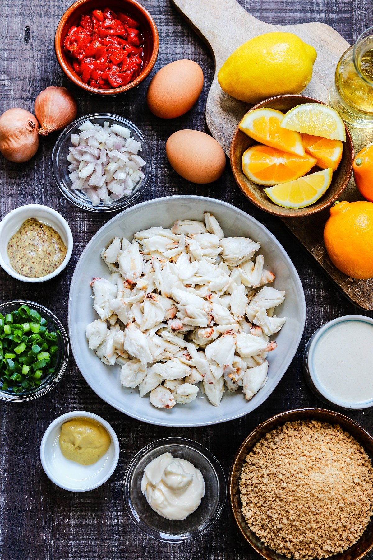 Lump crab meat and other ingredients in bowls on wooden surface.