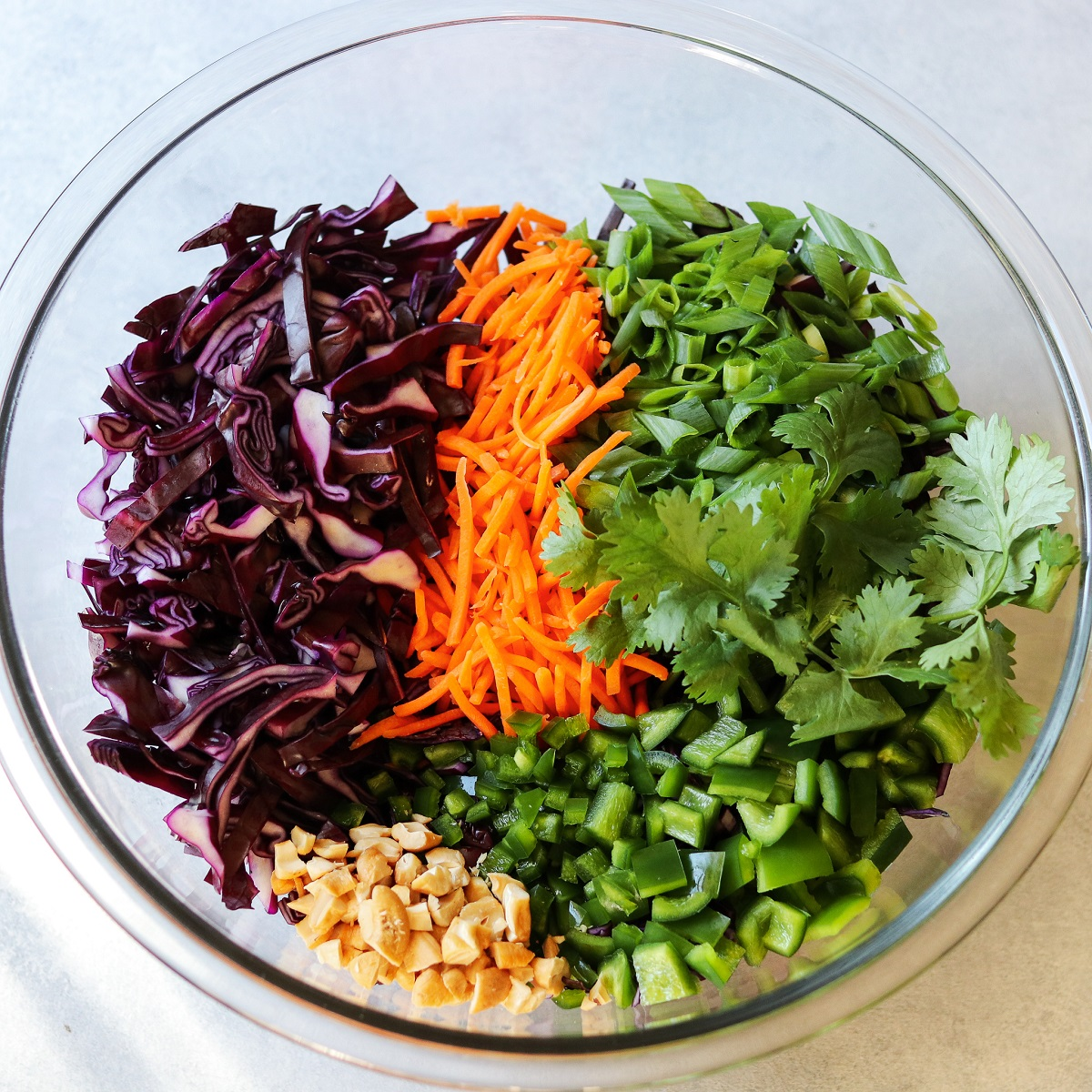 Slaw ingredients piled in large glass bowl ready to be mixed.