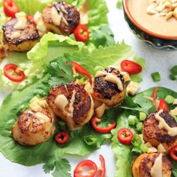 Seared scallops wrapped in bibb lettuce leaves and garnished with sliced fresno peppers.