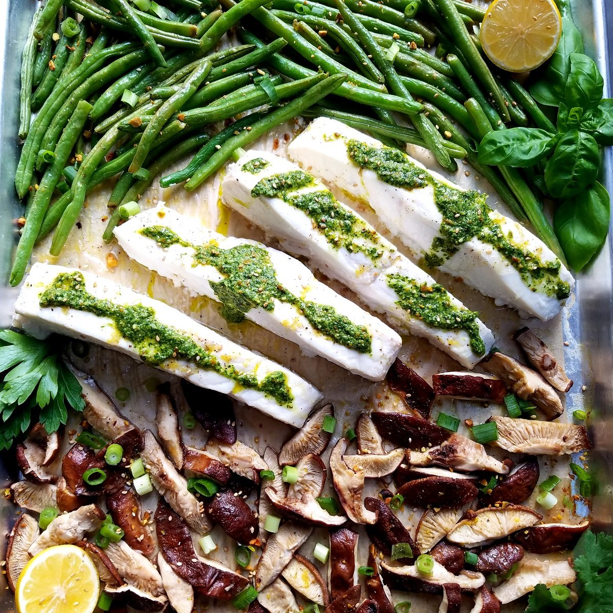 Roasted halibut and vegetables topped with pesto and served from sheet pan.