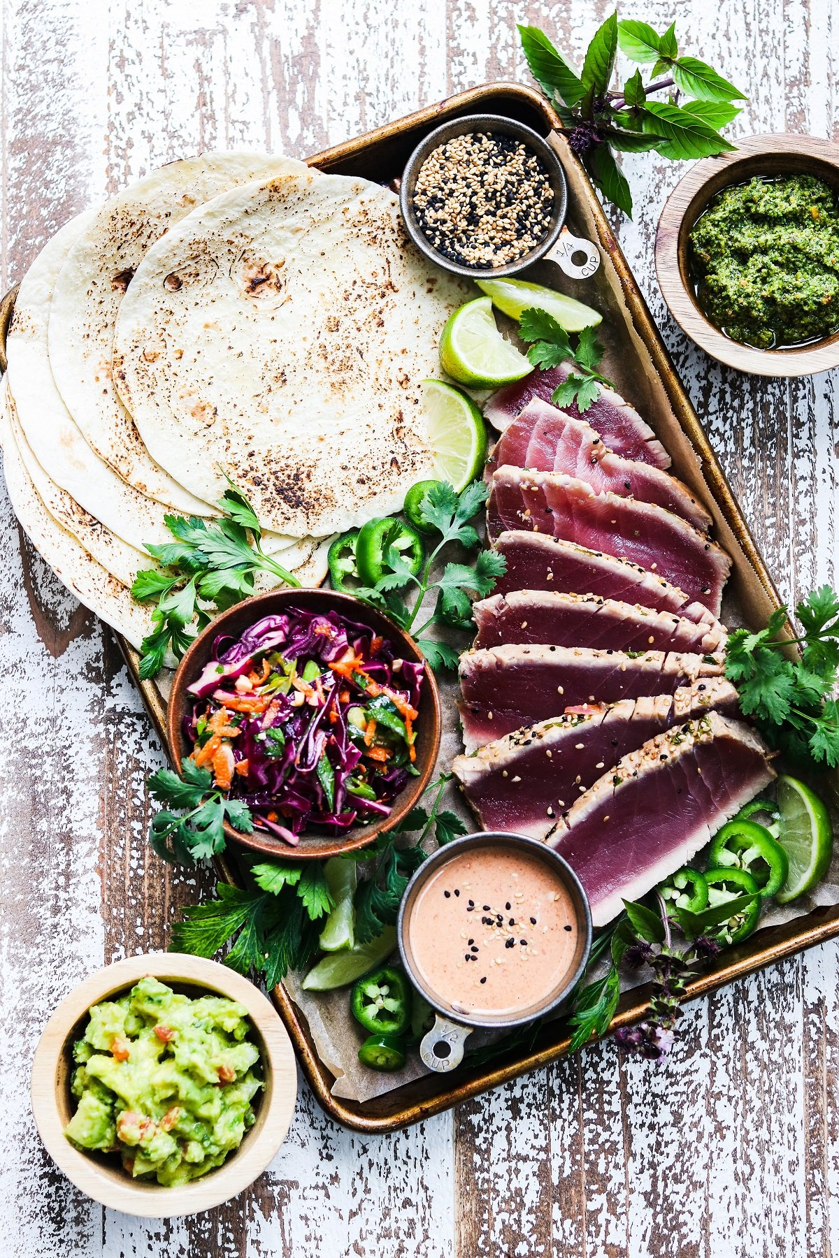 Seared ahi tuna arranged on baking sheet with tortillas, slaw and other taco fixings.