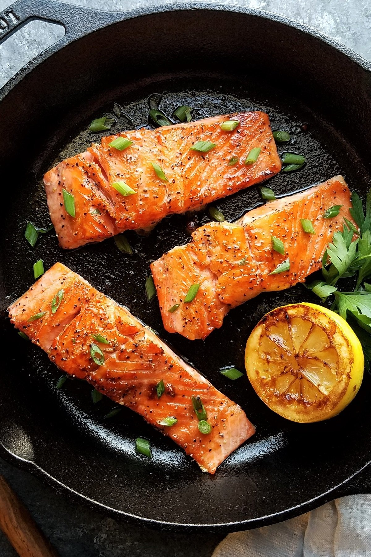 Perfectly seared salmon fillets in cast iron skillet with charred lemon