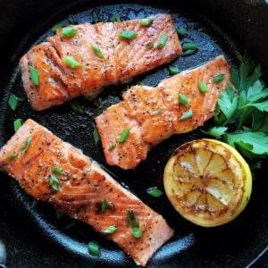 Caramelized salmon garnished with sliced green onion.