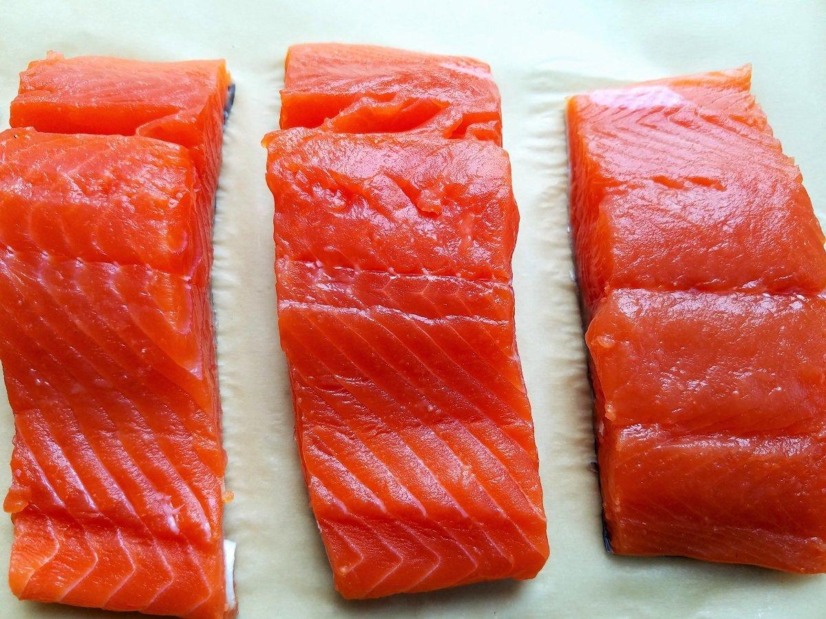 Fresh coho salmon fillets on parchment paper.