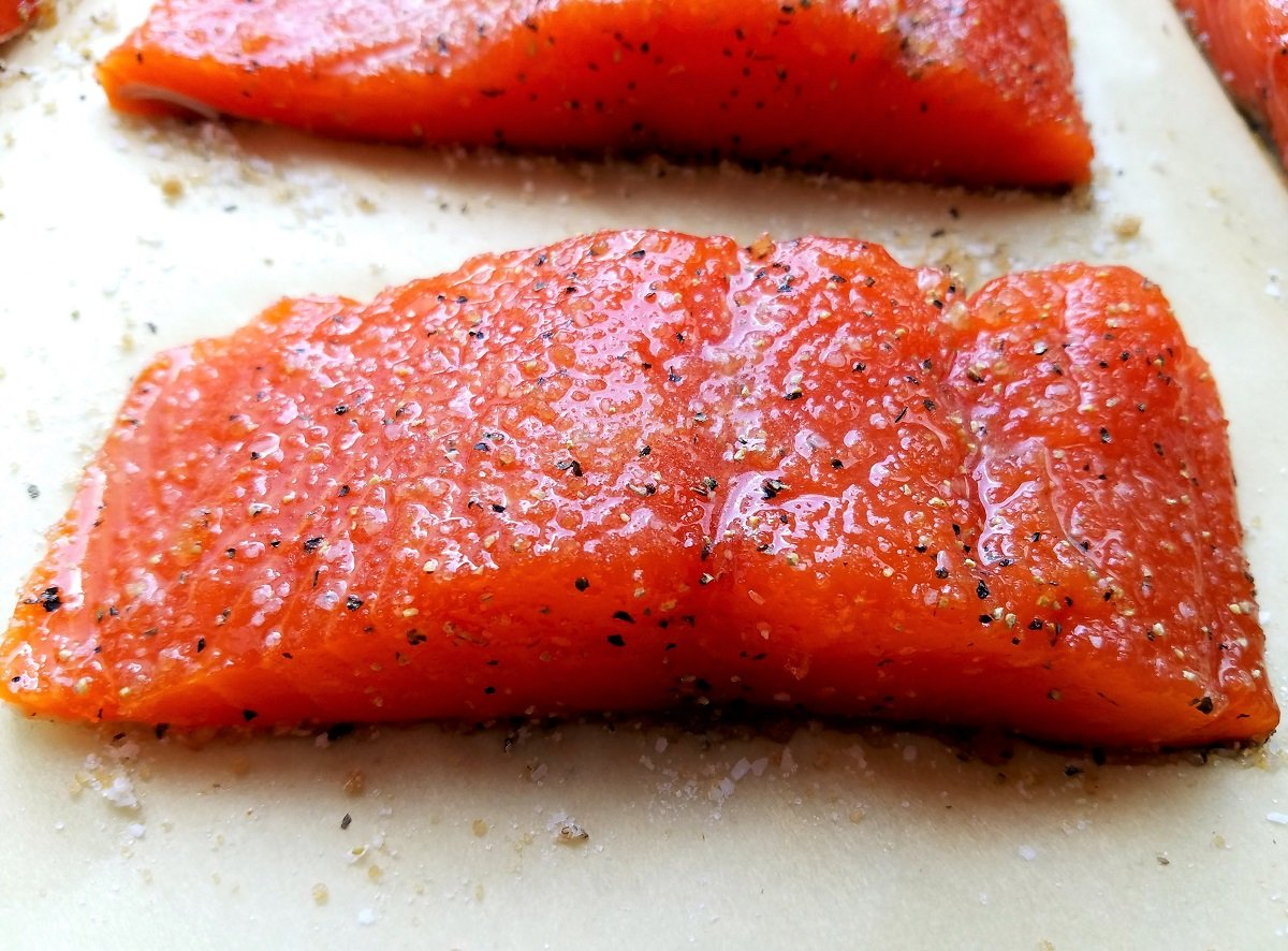 Close up of salmon fillet seasoned with salt, pepper and granulated sugar.