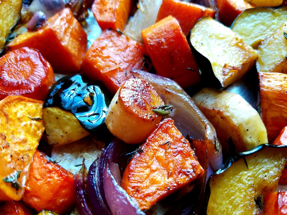 Close up of baked parsnips, acorn squash, sweet potatoes, carrots and red onion.