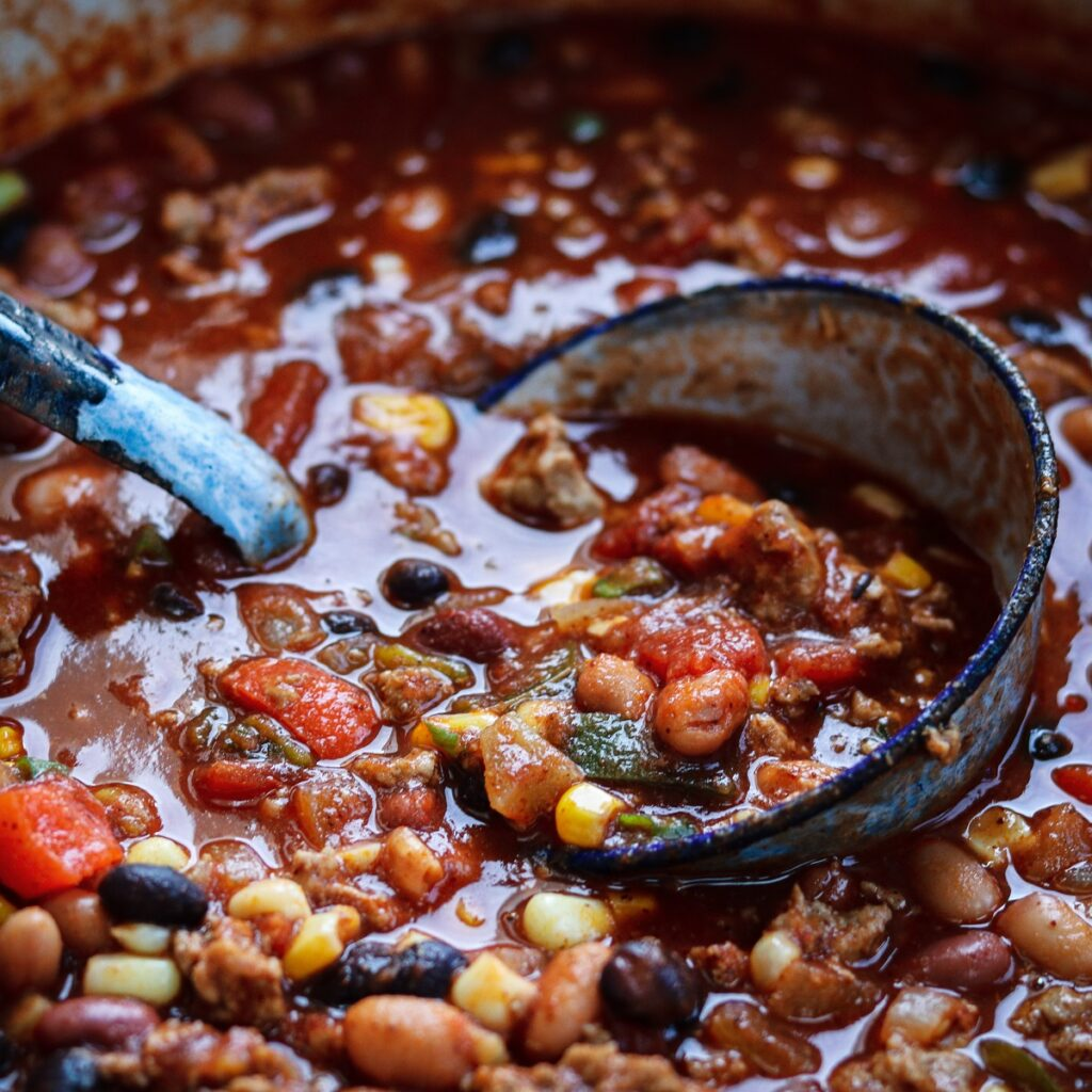 Ladling hearty chili from dutch oven pot.