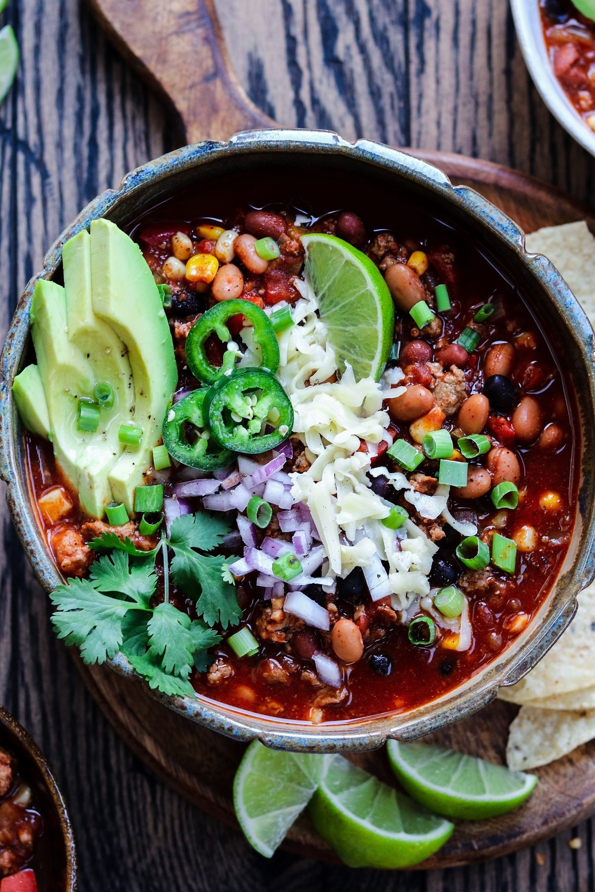 Turkey chili garnished with lime wedges and cilantro, served with tortilla chips.