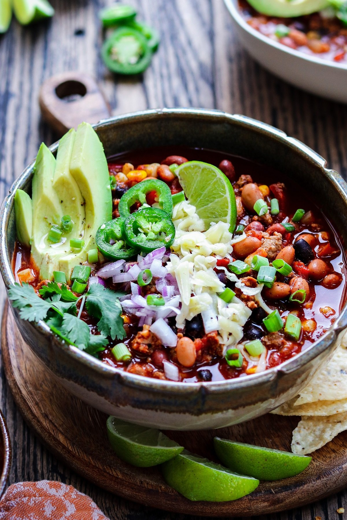 Gluten-free chili with garnishes served on wooden charger.
