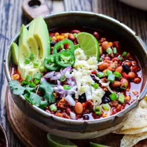 Healthy turkey chili with chopped red and green onions.