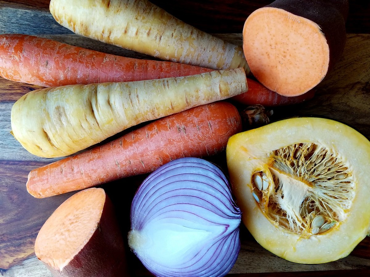 Whole carrots and parsnips on wooden board along with halved sweet potatoes, acorn squash and red onion.